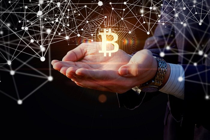 Hands holding a Bitcoin symbol.