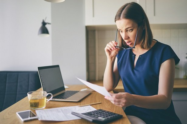 woman at computer holding paper and looking dismayed