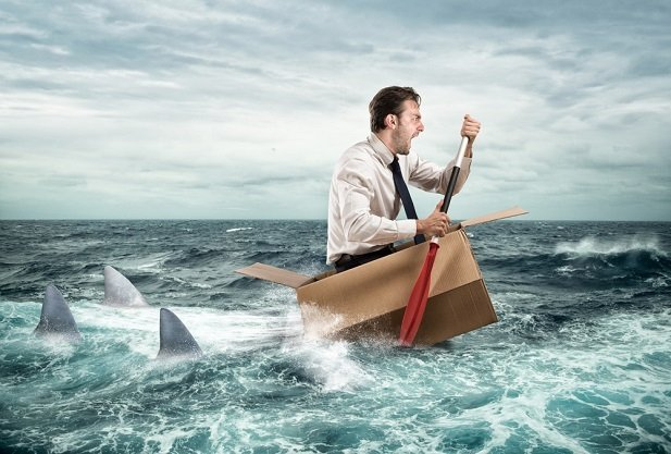 business man in tiny boat trying to row away from sharks