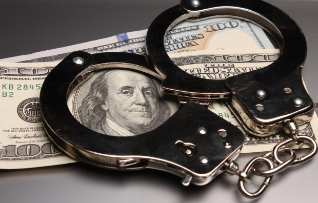 image of handcuffs on top of cash