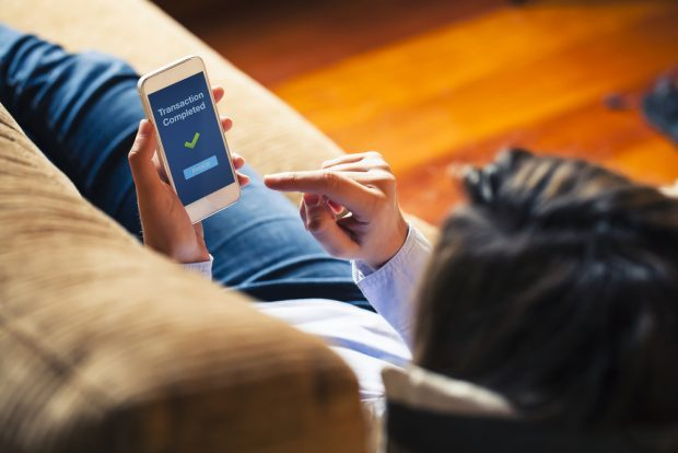 Woman using mobile banking from couch