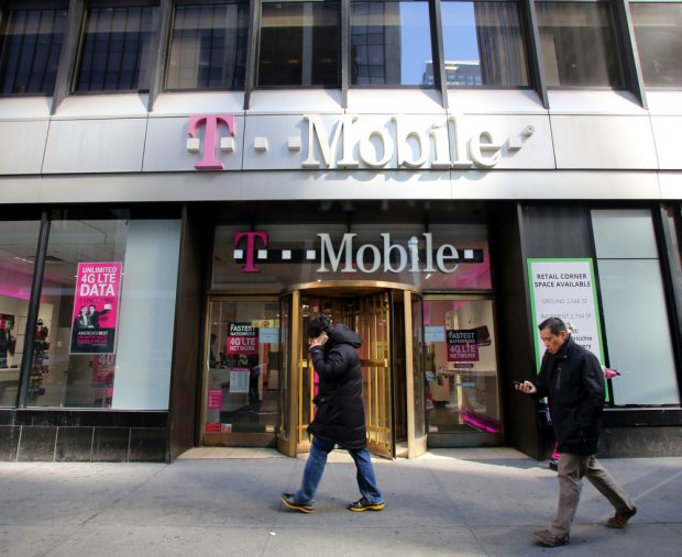 Pedestrians walk past a T-Mobile retail store