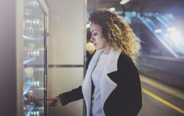 Woman using a cashless vending machine