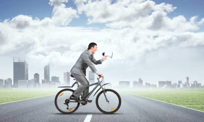 Businessman on bike with megaphone