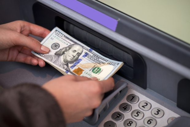 Depositing money into an ATM.