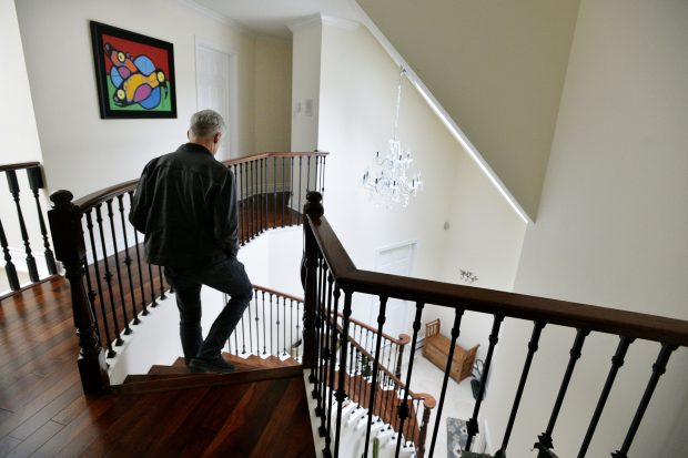 man walking down stairs of his home
