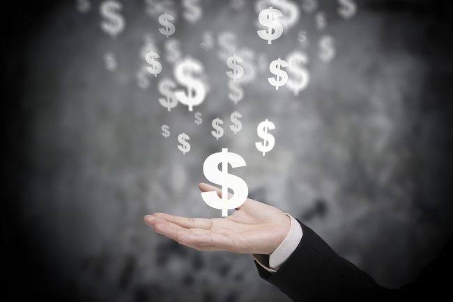 Executive's hand catching dollar signs