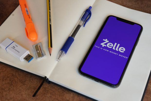 Zelle app open with smartphone sitting on notebook