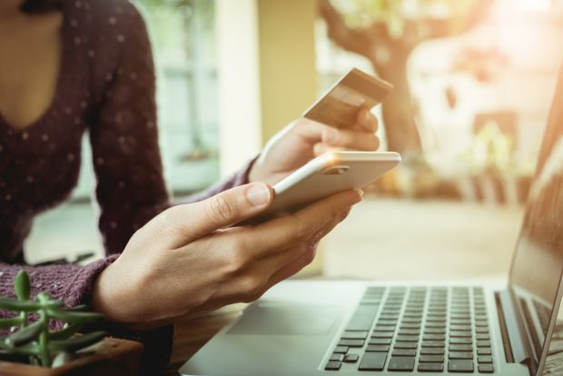Woman using credit card to shop on her smartphone