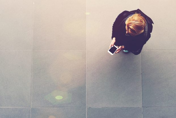 Woman stands alone in a large space while conducting mobile banking on her phone.