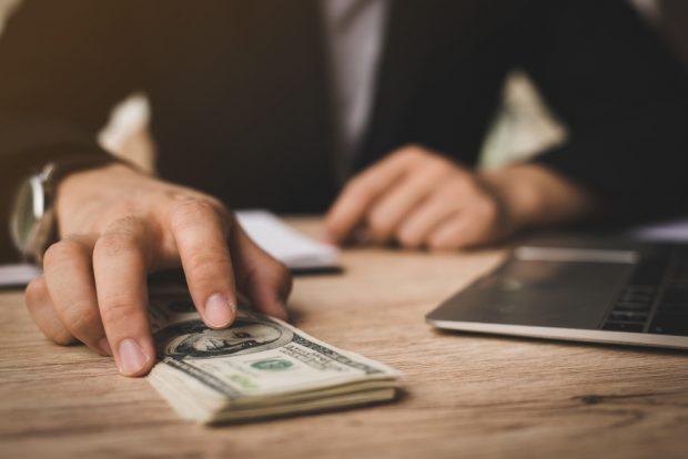 Man slides stack of cash across desk to member.