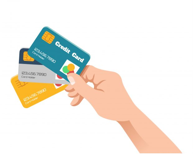Hand holding credit and debit cards.