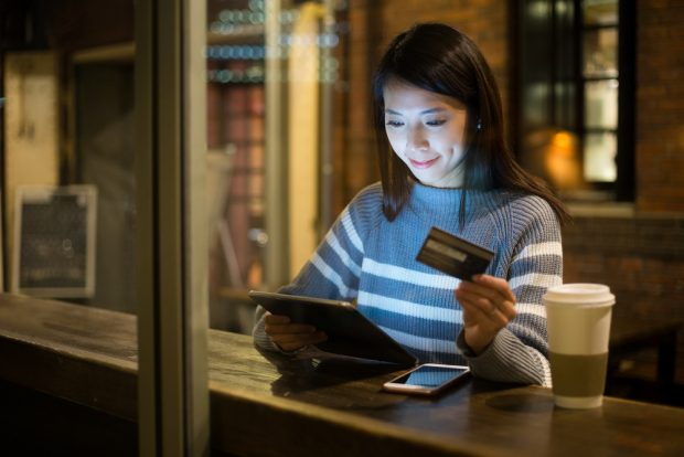 woman using credit card to make a mobile purchase