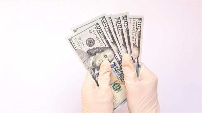 Gloved hands holding cash