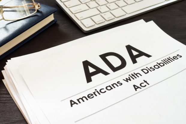 Copy of the Americans with Disabilities Act sitting next to a computer keyboard.