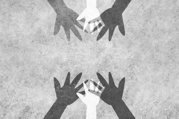 Hands reaching in to unite against racism.