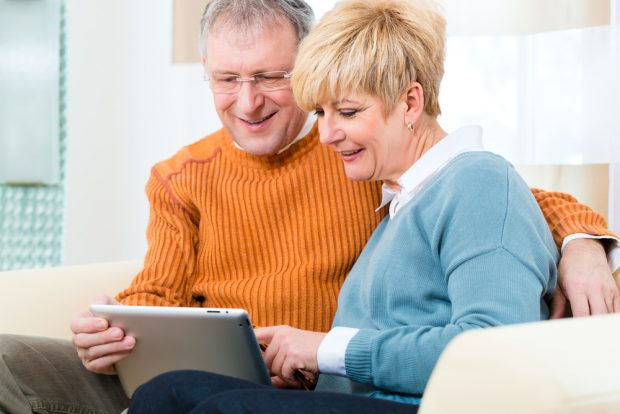 couple sitting on the couch looking at their finances