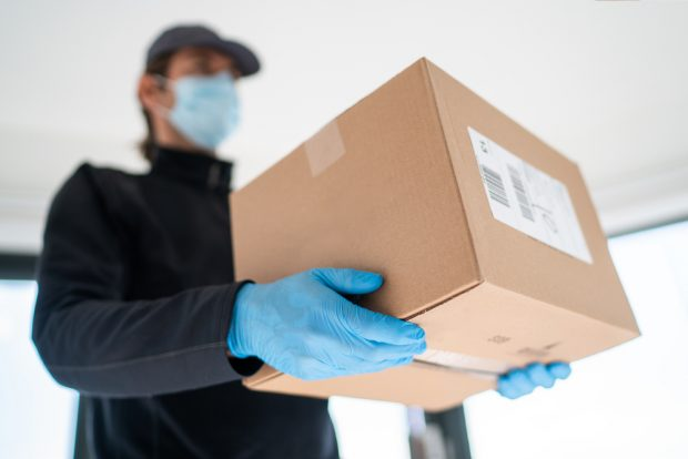 packaged being delivered to door by man wearing gloves and a mask