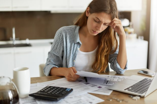 Woman looking at bills worrying how she will pay.