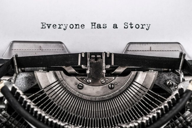 "Typewriter with ""everyone has a story"" text"