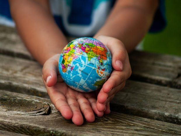 child in developing country holding the earth in his hands