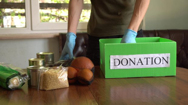 Man loading in donated food into a donation box.