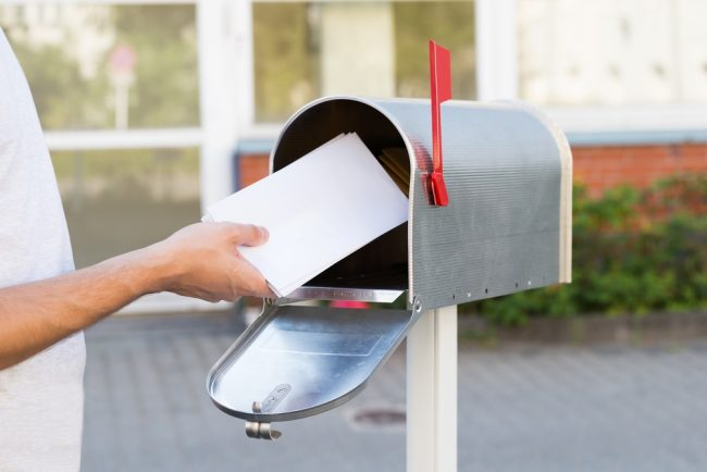 Person removing envelopes from mailbox