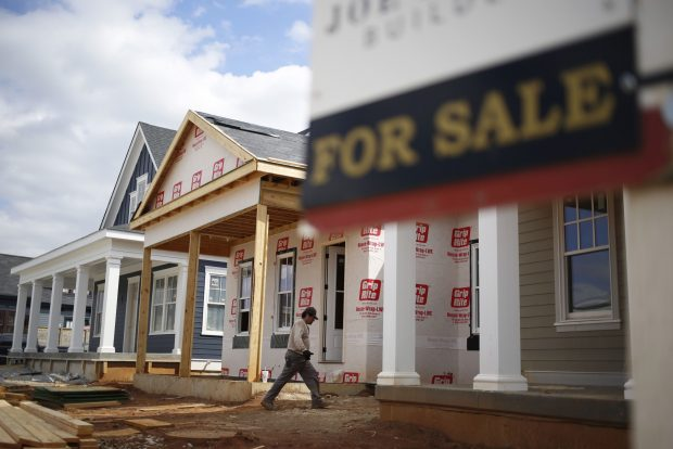 """A contractor walks past a """"For Sale"""" sign while working on a home under construction in the Norton Commons subdivision in Louisville, Ky."""