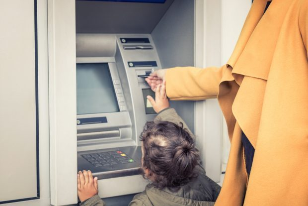 small child helping parent at the ATM