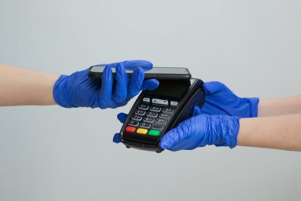 consumer wearing gloves using a smartphone to make a contactless payment.