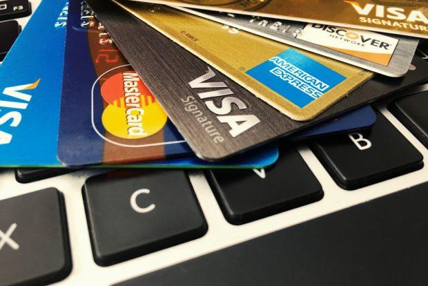close-up image of Visa, Mastercard, American Express cards on a computer keyboard.