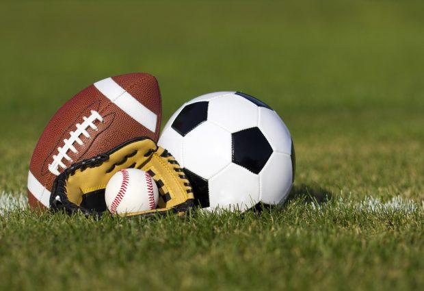 A football, baseball and baseball glove, soccer ball sitting on the grass.