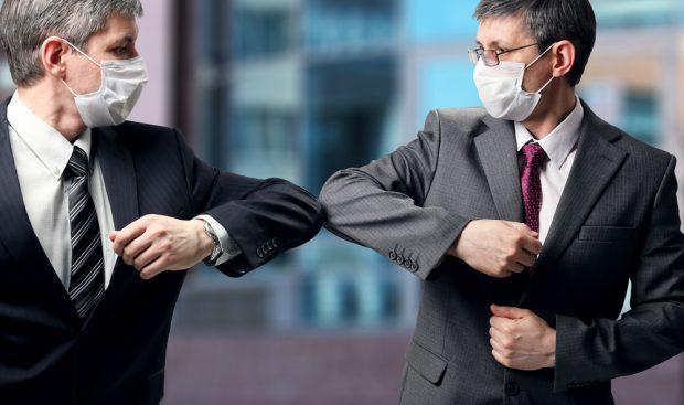 Two men wearing masks bumping elbows instead of shaking hands.