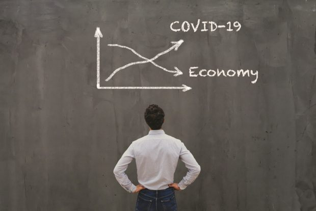 man looking at a chart showing growth of COVID 19 and a decline in the economy