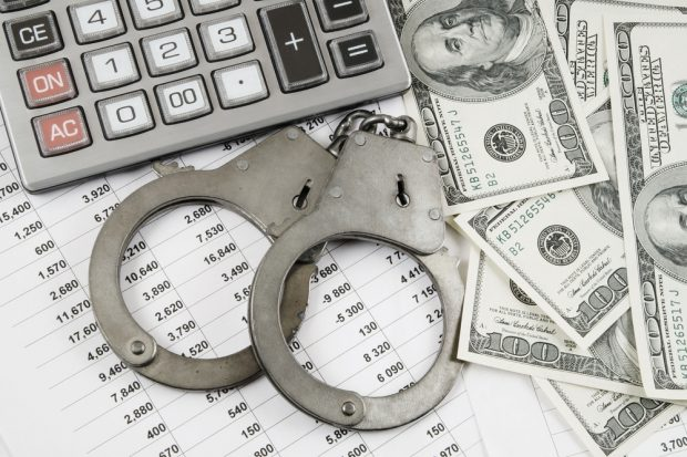 photo of a calculator, handcuffs, cash and a spreadsheet
