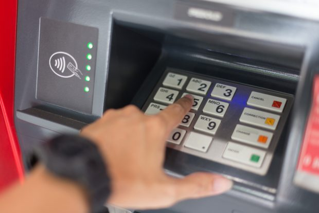 Person putting in PIN at ATM