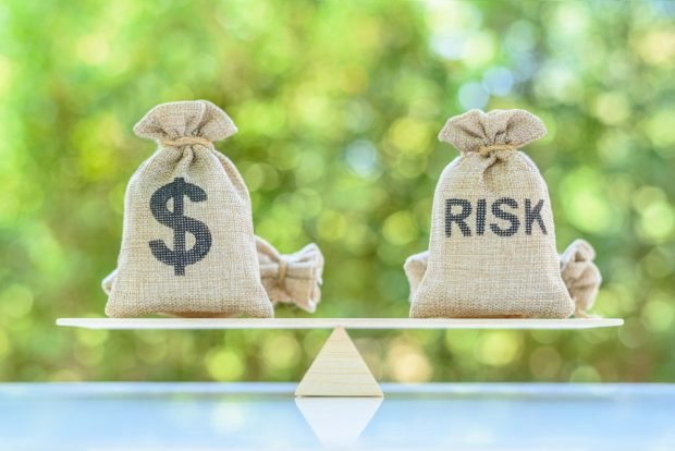 Dollar and risk bags on basic balance scale