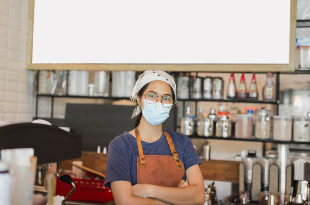 Woman who owns coffee shop wearing a mask.