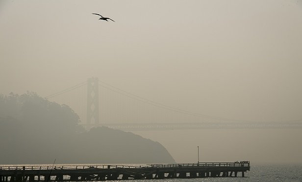 The San Francisco Oakland Bay Bridge is obscured by smoke from wildfires in San Francisco, California, U.S., on Friday, Nov. 16, 2018. The Camp Fire, burning about 90 miles (145 kilometers) north of Sacramento, has killed more than 60 people and destroyed thousands of homes since it began last week. Photographer: David Paul Morris/Bloomberg