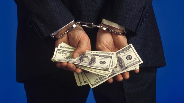 Handcuffed man holding cash.