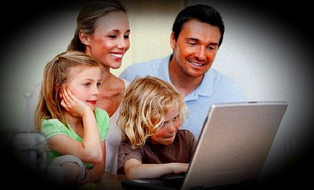 A couple with two children and a laptop; based on Shutterstock image 91952378