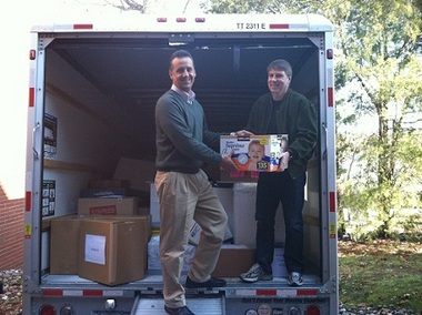 NJCUL's Paul Gentile, left, and NCUA's Buddy Gill unload the truck of donated goods at NJCUL's headquarters in Hightstown, N.J.