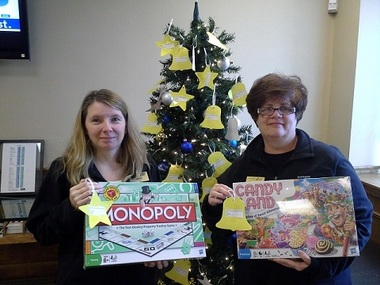 Winthrop Federal Branch Supervisor Denise Grassa, left, and Assistant Branch Manager and Loan Officer Maria McCue with some of the items already purchased for area children and teenagers as part of the credit union's Giving Tree.