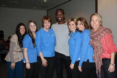 The Patriots' Brandon Lloyd with members of Jeanne D'Arc Credit Union's Financial Education team and Lowell High School branch staff, from left, Nicole Bedard, Jessica Aller, Assistant Vice President-Financial Education Anne-Marie Bisson, Kim Beaulieu, Leisa Brito and Heather Pintal.